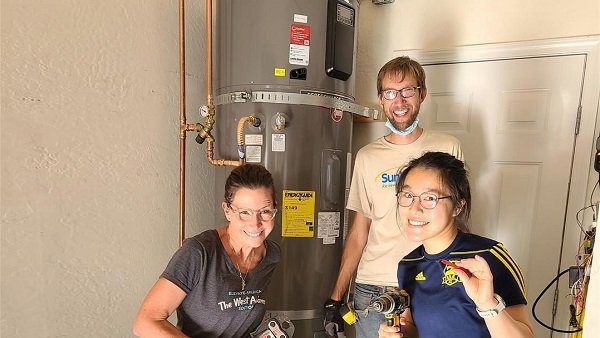 Volunteers installing heat pump water heater